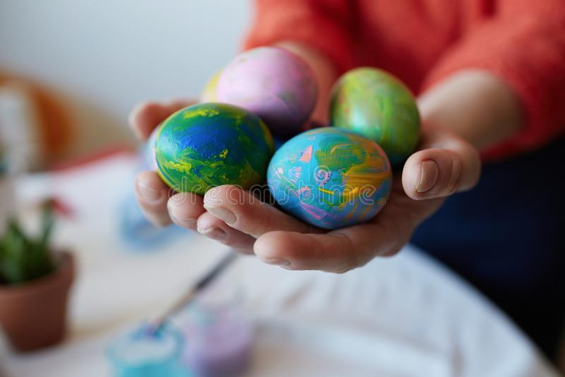 Θηλυκά χέρια που κρατούν τα χρωματισμένα ζωηρόχρωμα αυγά Πάσχας Ευτυχής διακόσμηση Πάσχας στο γλυκό σπίτι στοκ εικόνα με δικαίωμα ελεύθερης χρήσης