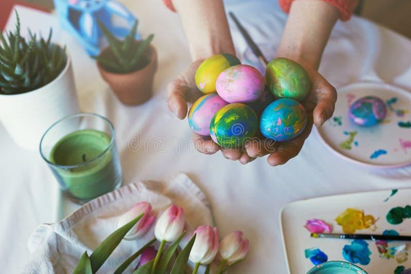 Θηλυκά χέρια που κρατούν τα χρωματισμένα ζωηρόχρωμα αυγά Πάσχας Ευτυχής διακόσμηση Πάσχας στο γλυκό σπίτι στοκ εικόνες με δικαίωμα ελεύθερης χρήσης