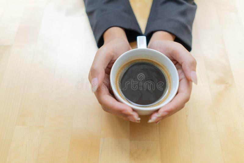 Θηλυκά χέρια που κρατούν το φλυτζάνι καφέ στον καφέ, τοπ άποψη Κούπα καφέ κατανάλωσης γυναικών με τον αφρό στη καφετερία πέρα από στοκ φωτογραφία με δικαίωμα ελεύθερης χρήσης