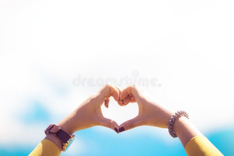 Θηλυκή διαμόρφωση μορφής καρδιών χεριών στο μπλε ουρανό στοκ εικόνες