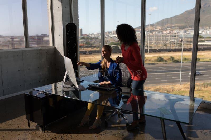 Θηλυκοί ανώτεροι υπάλληλοι που εργάζονται στον προσωπικό υπολογιστή γραφείου στο γραφείο στην αρχή στοκ εικόνες
