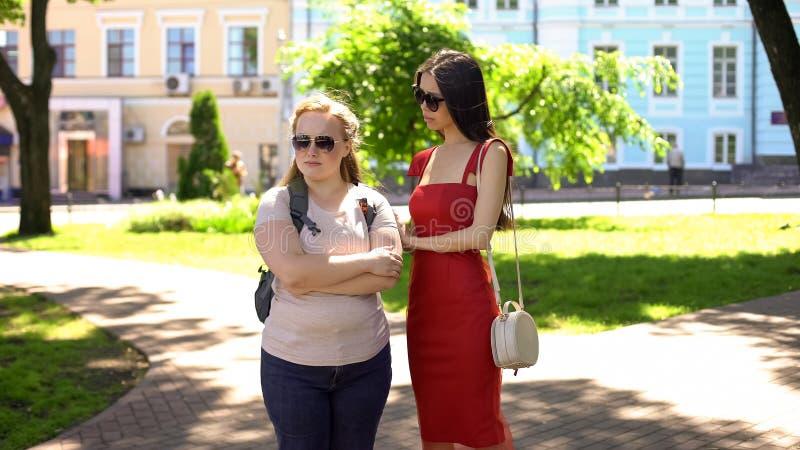 Θηλυκοί φίλοι που υποστηρίζουν στο πάρκο, σύγκρουση βασισμένη στο φθόνο, αβεβαιότητες εμφάνισης στοκ φωτογραφίες