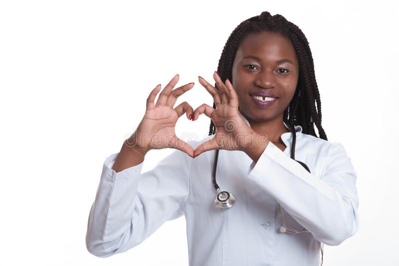 Θηλυκός αμερικανικός αφρικανικός γιατρός, γυναίκα νοσοκόμων που φορά το ιατρικό παλτό με το στηθοσκόπιο που κάνει την καρδιά με τ στοκ εικόνες με δικαίωμα ελεύθερης χρήσης