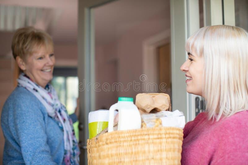 Θηλυκός γείτονας που βοηθά την ανώτερη γυναίκα με τις αγορές στοκ εικόνες
