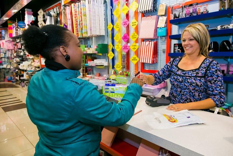 Θηλυκός λιανικός αγοραστής που πληρώνει με μια πιστωτική κάρτα στοκ φωτογραφίες με δικαίωμα ελεύθερης χρήσης