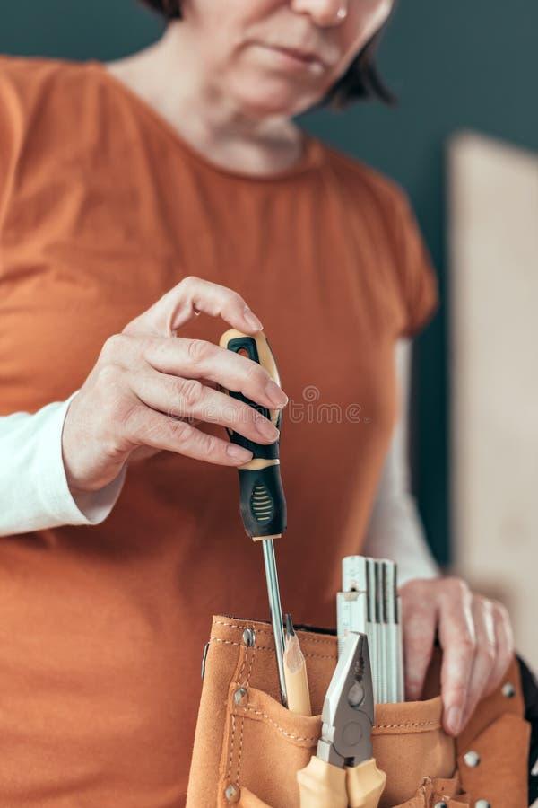 Θηλυκός ξυλουργός που οργανώνει το σύνολο ζωνών εργαλείων στοκ εικόνα με δικαίωμα ελεύθερης χρήσης