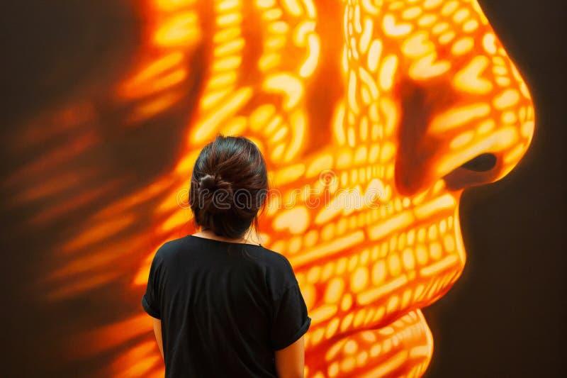 Θηλυκός τουρίστας στο μαύρο ιματισμό που στέκεται και που εξετάζει τη σύγχρονη τέχνη του ανθρώπινου προσώπου Φανταστικός φωτισμός στοκ φωτογραφία