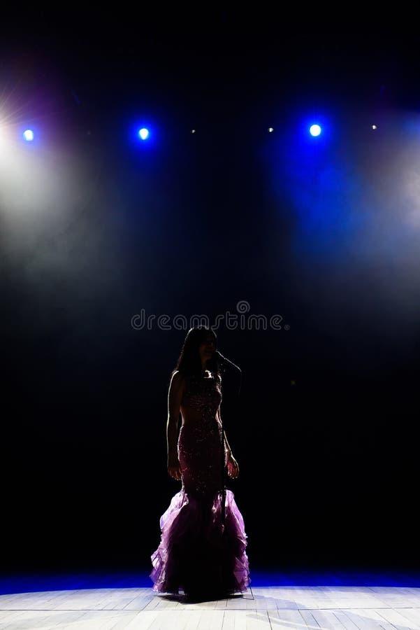 Θηλυκός τραγουδιστής στο στάδιο που κρατά ένα μικρόφωνο στοκ εικόνες