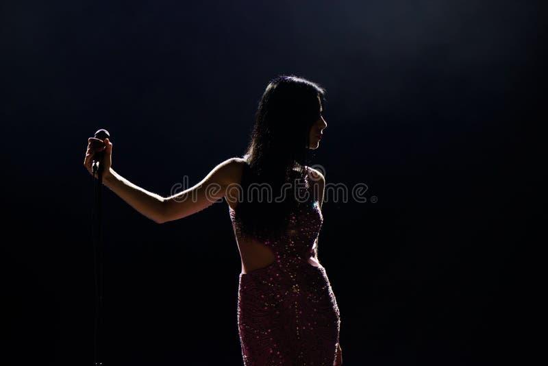 Θηλυκός τραγουδιστής στο στάδιο που κρατά ένα μικρόφωνο στοκ φωτογραφία με δικαίωμα ελεύθερης χρήσης