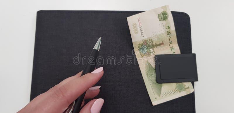 Θηλυκό χέρι που κρατά τη μαύρη μάνδρα στο μαύρο φάκελλο στοκ φωτογραφία