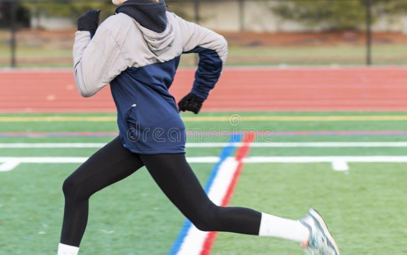 Θηλυκό sprinter στον τομέα τύρφης κατά τη διάρκεια της χειμερινής πρακτικής στοκ εικόνα