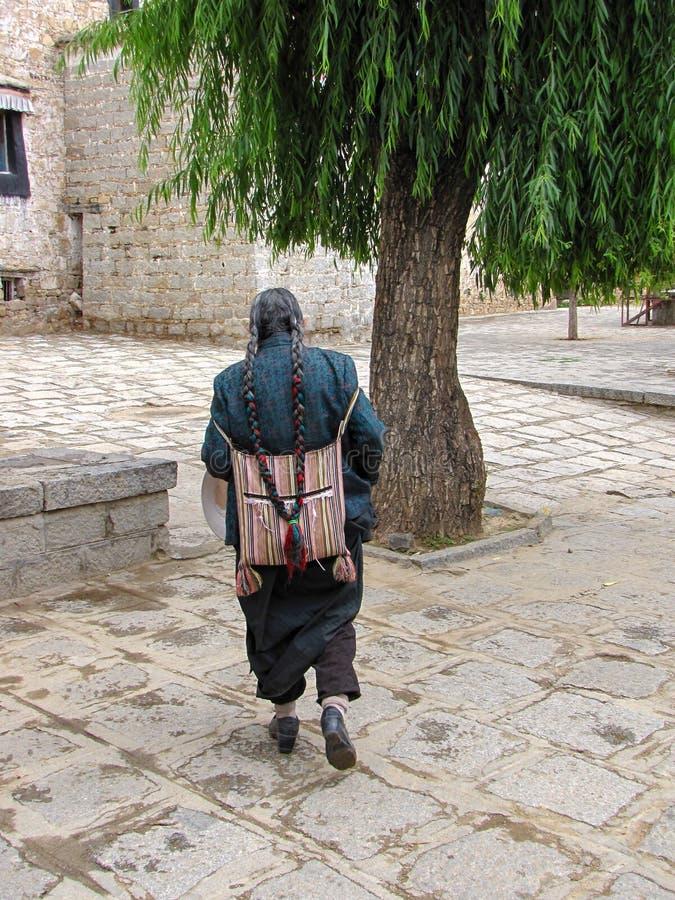 Θιβετιανό άτομο με τις πλεξούδες στα παραδοσιακά ενδύματα που περπατά κοντά στο μοναστήρι ορών, Lhasa, Θιβέτ, Κίνα στοκ φωτογραφία