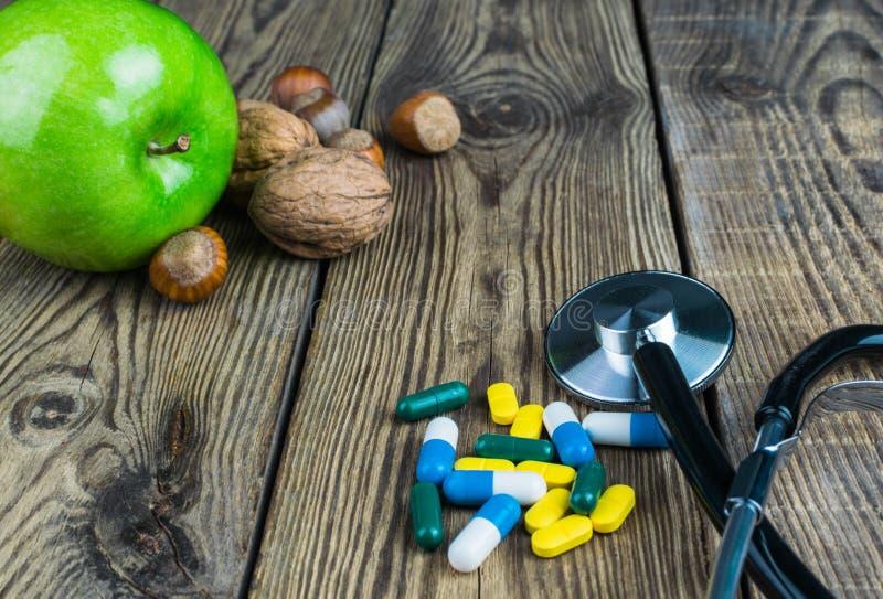 Ιατρικό στηθοσκόπιο, πράσινα μήλο και καρύδια στο ξύλινο υπόβαθρο στοκ εικόνα