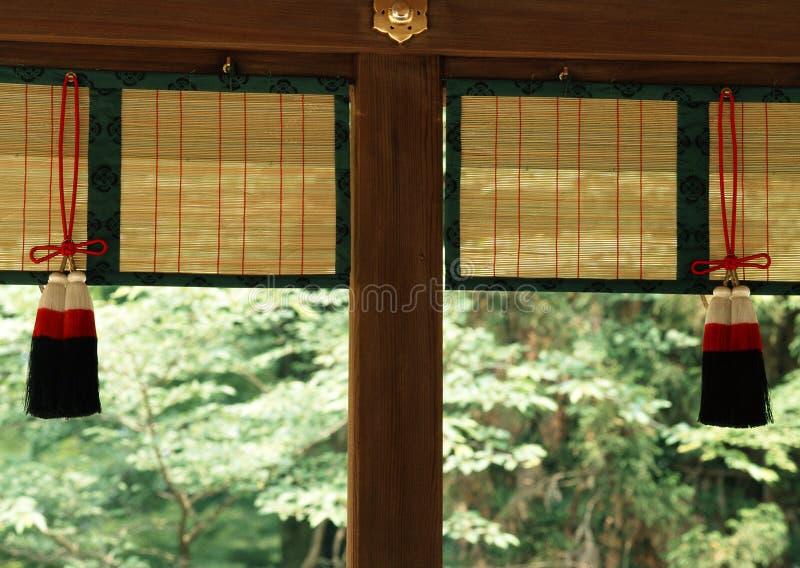 Ιαπωνικά αρχιτεκτονικά διακοσμητικά στοιχεία που κρεμούν μαζί με το ξύλινο υπόβαθρο εργασιών στοκ εικόνα