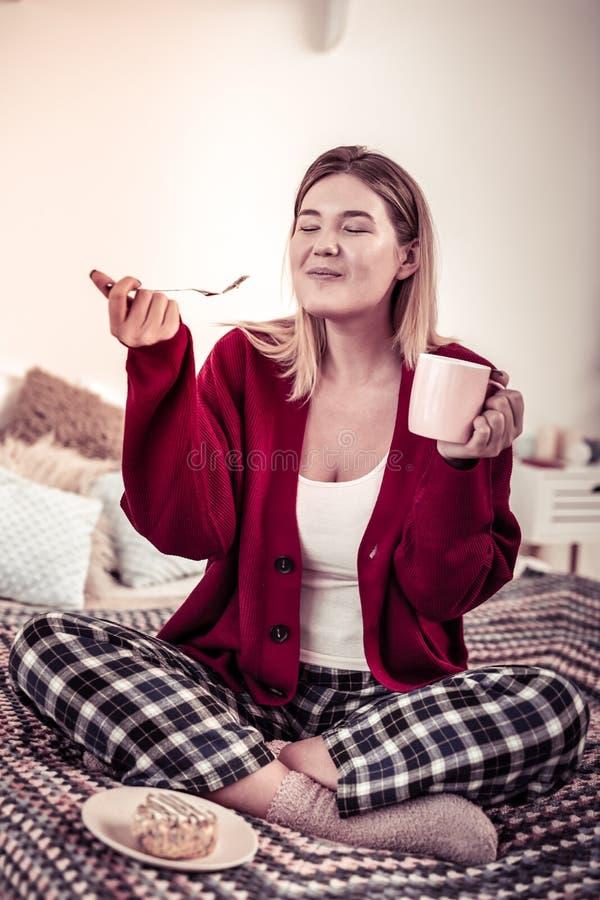 Ικανοποιημένη ευτυχής γυναίκα που είναι εξαιρετικά ευχάριστη με το γούστο του κέικ στοκ φωτογραφία με δικαίωμα ελεύθερης χρήσης