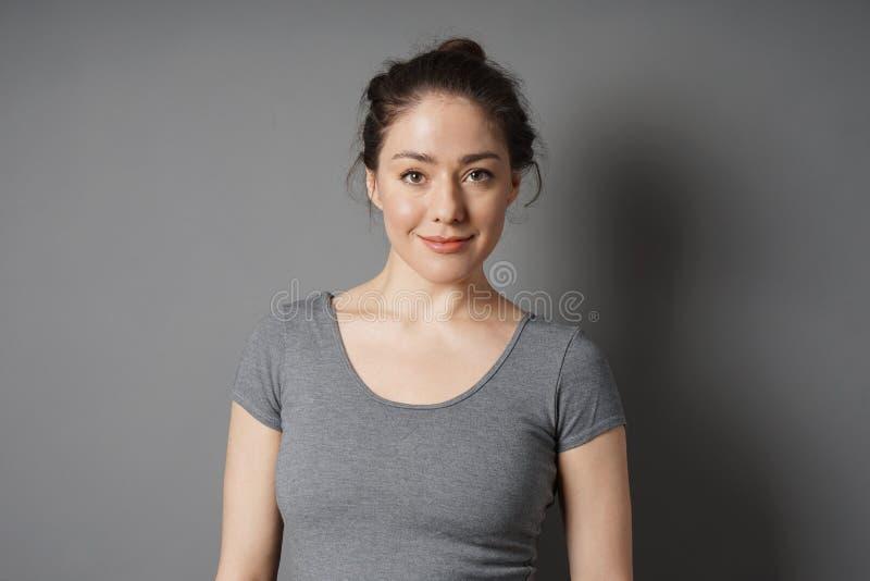 Ικανοποιημένη νέα γυναίκα με το ακατάστατο κουλούρι τρίχας brunette στοκ εικόνα