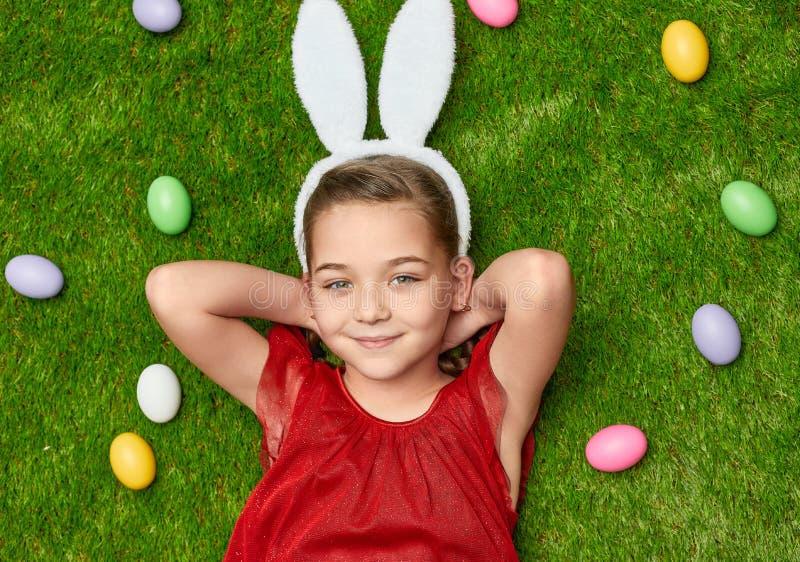 Ικανοποιημένο κορίτσι στα αυτιά λαγουδάκι που χαλαρώνει στο πράσινο λιβάδι στοκ εικόνες