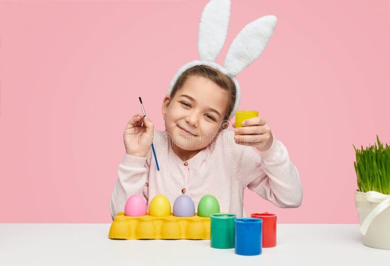 Ικανοποιημένο κορίτσι παιδιών με τα αυγά και τα χρώματα στοκ εικόνα