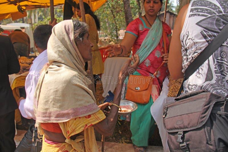 Ινδία, GOA, στις 28 Ιανουαρίου 2018 Η φτωχή γυναίκα ζητά τα χρήματα στην οδό στην Ινδία Μια γυναίκα επαιτών με το χέρι ένδεια στοκ εικόνα