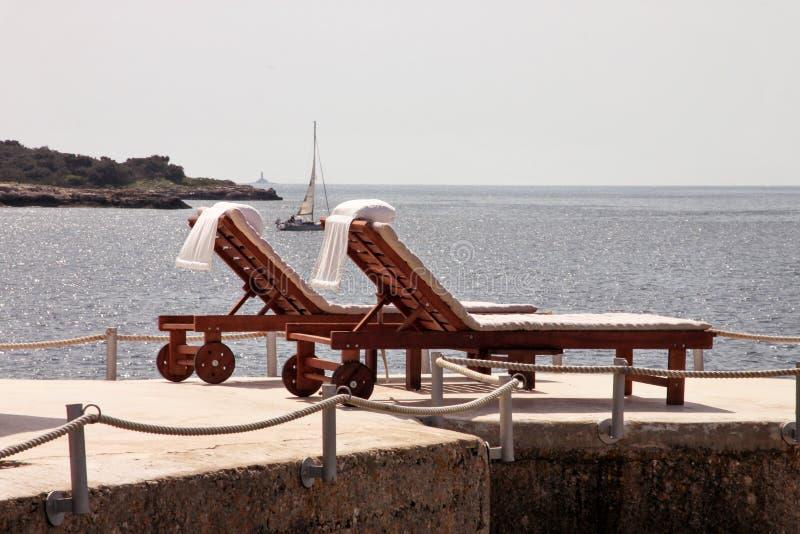 Ιδιωτικές παραλίες στη Μεσόγειο Έδρες, καρέκλες γεφυρών, αργόσχολοι ήλιων και parasols αναμονή τους τουρίστες στοκ εικόνα με δικαίωμα ελεύθερης χρήσης