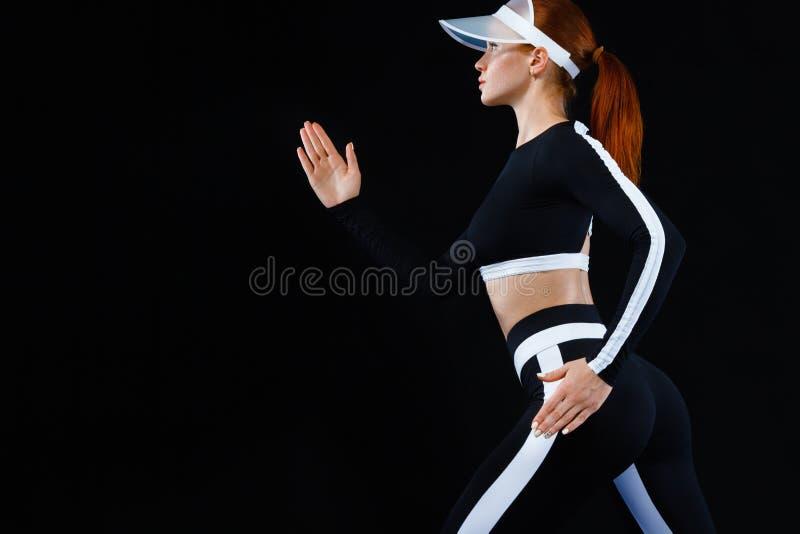 Ισχυρή αθλητική γυναίκα sprinter, τρέχοντας στο μαύρο υπόβαθρο που φορά sportswear Ικανότητα και αθλητικό κίνητρο τρέξιμο στοκ εικόνες