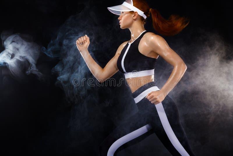 Ισχυρή αθλητική γυναίκα sprinter, τρέχοντας στο μαύρο υπόβαθρο που φορά sportswear Ικανότητα και αθλητικό κίνητρο τρέξιμο στοκ φωτογραφίες