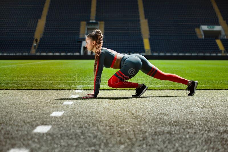 Ισχυρή αθλητική γυναίκα sprinter, τρέχοντας στο στάδιο που φορά sportswear Ικανότητα και αθλητικό κίνητρο Έννοια δρομέων στοκ εικόνες με δικαίωμα ελεύθερης χρήσης