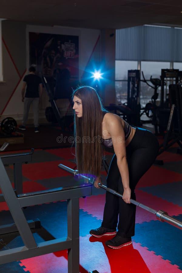 Ισχυροί γυναίκα και άνδρας που κρατούν τα βαριά barbells στη γυμναστική Οριζόντιος πυροβοληθείς στο εσωτερικό στοκ φωτογραφία με δικαίωμα ελεύθερης χρήσης