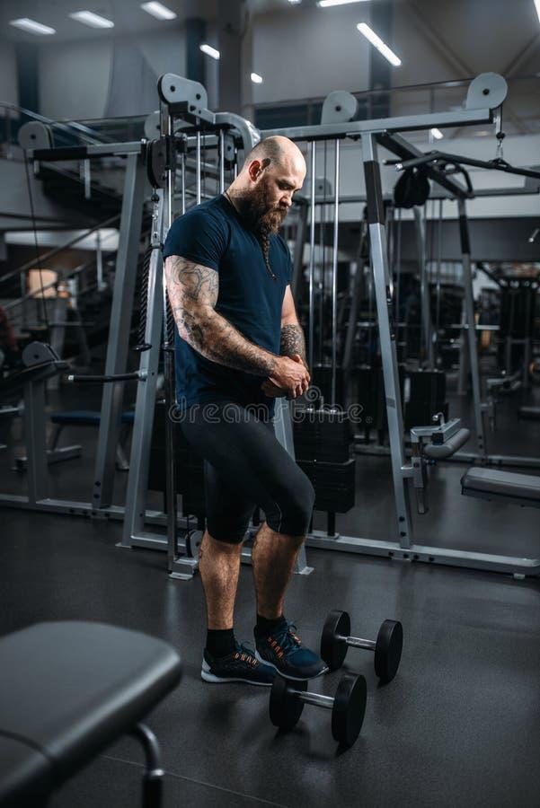 Ισχυρός αθλητής με τους αλτήρες, που εκπαιδεύουν στη γυμναστική στοκ φωτογραφία