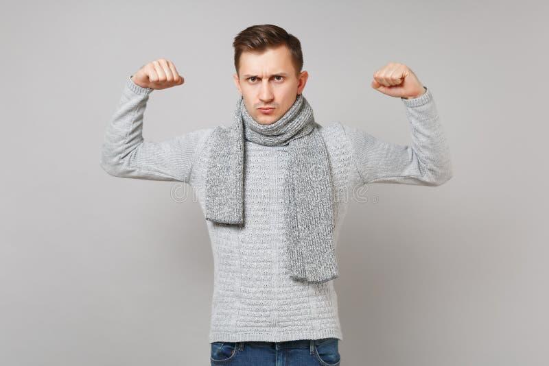 Ισχυρός νεαρός άνδρας στο γκρίζο πουλόβερ, μαντίλι που παρουσιάζει δικέφαλους μυς, μυ'ες στο γκρίζο υπόβαθρο τοίχων στο στούντιο  στοκ φωτογραφία