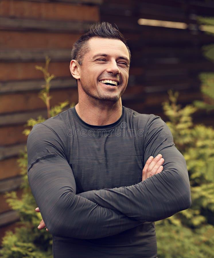 Ισχυρό όμορφο άτομο που γελά και που κοιτάζει υπόβαθρο θερινών στο πράσινο δέντρων με τα διπλωμένα όπλα closeup στοκ εικόνες με δικαίωμα ελεύθερης χρήσης