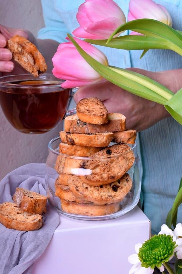Ιταλικά μπισκότα Biscotti σε ένα βάζο γυαλιού και μια γυναίκα με ένα φλυτζάνι του τσαγιού στοκ εικόνες με δικαίωμα ελεύθερης χρήσης