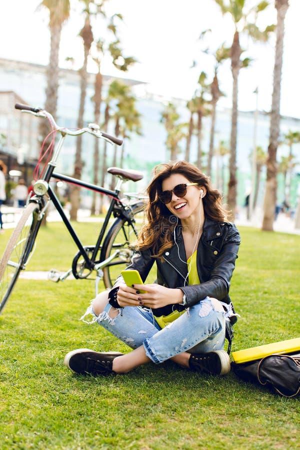 Κάθετο κορίτσι brunette φωτογραφιών στα γυαλιά ηλίου που κάθεται στη χλόη κοντά στο ποδήλατο στο υπόβαθρο φοινικών Φορά τα σχισμέ στοκ φωτογραφία με δικαίωμα ελεύθερης χρήσης