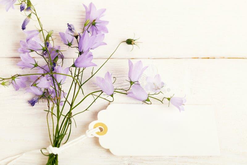 Κάρτα ημέρας μητέρων με με μια ανθοδέσμη του λεπτού campanula wildflowers στο λευκό ξύλινο πίνακα στοκ φωτογραφία με δικαίωμα ελεύθερης χρήσης