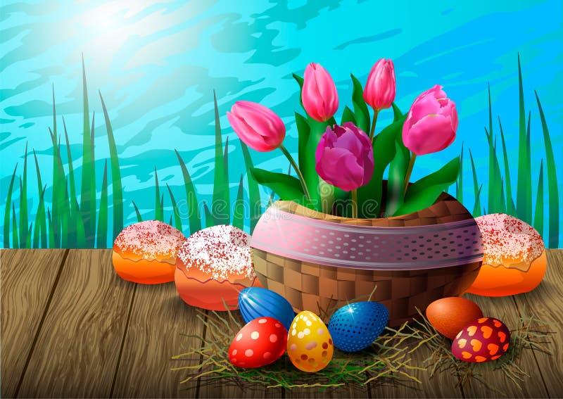 Κάρτα με τις τουλίπες σε ένα ψάθινο καλάθι, αυγά Πάσχας και cupcakes σε έναν ξύλινο πίνακα στα πλαίσια της χλόης και του ουρανού ελεύθερη απεικόνιση δικαιώματος