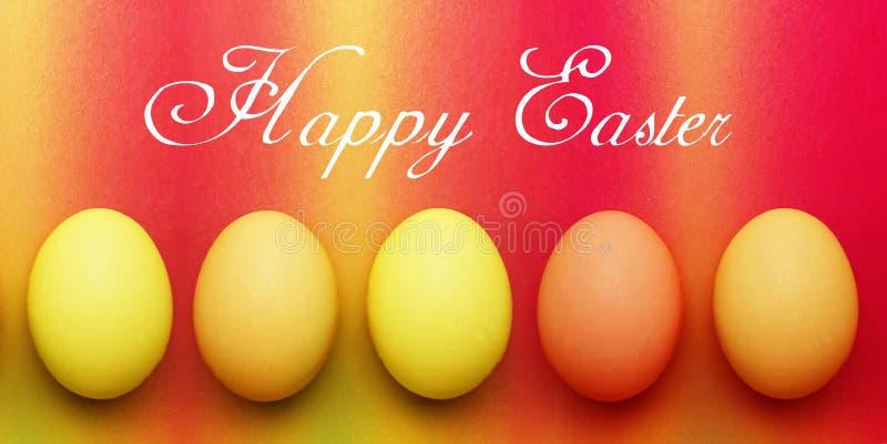 Κάρτα με πέντε βιολογικά οργανικά κόκκινα πορτοκαλιά κίτρινα αυγά Πάσχας σε ένα υπόβαθρο ουράνιων τόξων στοκ εικόνες