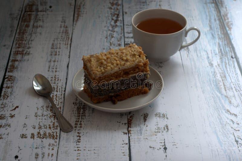Κέικ σφουγγαριών με τους σπόρους παπαρουνών σε ένα πιάτο, ένα κουτάλι και ένα φλυτζάνι του τσαγιού σε έναν ξύλινο πίνακα στοκ εικόνα με δικαίωμα ελεύθερης χρήσης