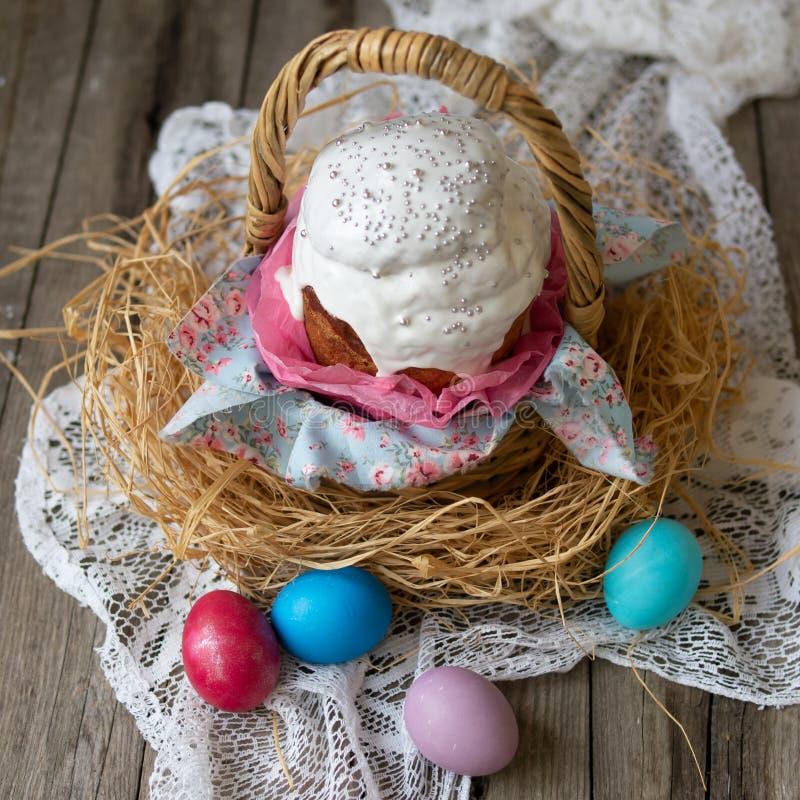Κέικ Πάσχας - kulich Το παραδοσιακό γλυκό ψωμί Πάσχας διακόσμησε την άσπρη τήξη στο καλάθι αχύρου και χρωμάτισε τα αυγά στην πετσ στοκ εικόνες