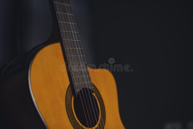 Κίτρινη acustic κιθάρα με το εκλεκτής ποιότητας μαύρο υπόβαθρο στοκ φωτογραφίες