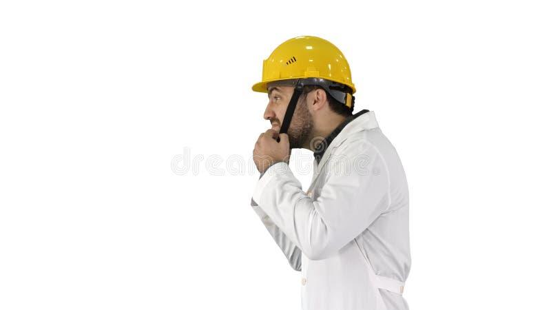Κίτρινο καπέλο κρανών ασφάλειας μηχανικών ή εργαζομένων που βάζει στο κεφάλι στο άσπρο υπόβαθρο στοκ εικόνες