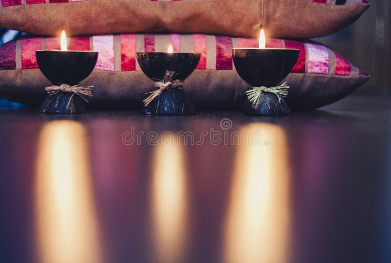 Καίγοντας κεριά αρώματος SPA κοχυλιών και burgundy καρύδων στα μαξιλάρια με το σχέδιο, άνετο εγχώριο εσωτερικό υπόβαθρο στοκ φωτογραφία με δικαίωμα ελεύθερης χρήσης