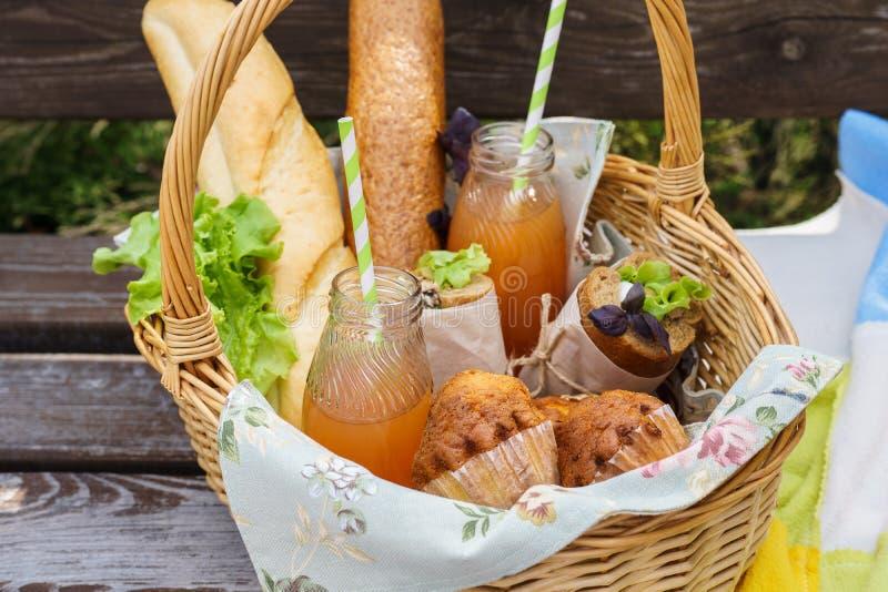 Καλάθι πικ-νίκ με τα τρόφιμα και ποτά σε έναν πάγκο πάρκων για το μεσημεριανό γεύμα στοκ εικόνες με δικαίωμα ελεύθερης χρήσης