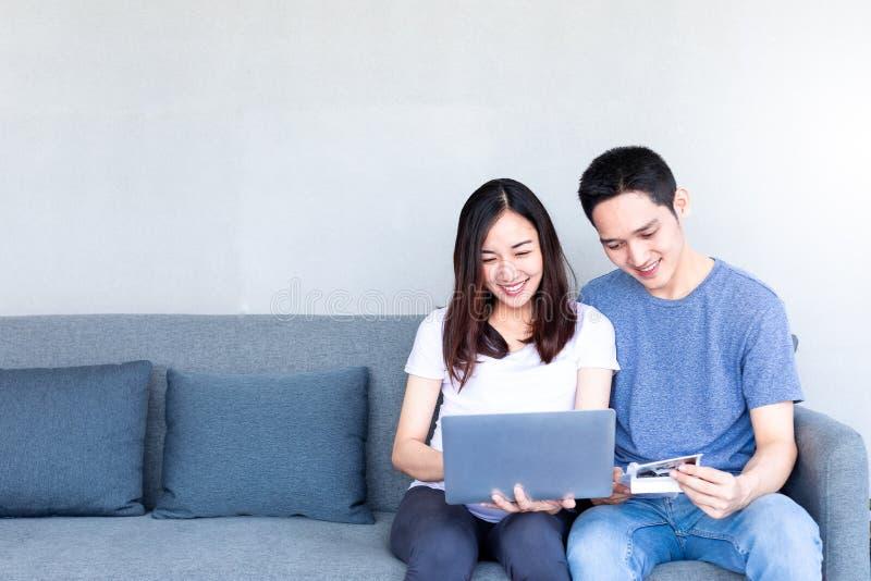Καλή νέα έγκυος συνεδρίαση ζευγών στον καναπέ με το φορητό προσωπικό υπολογιστή στοκ εικόνες