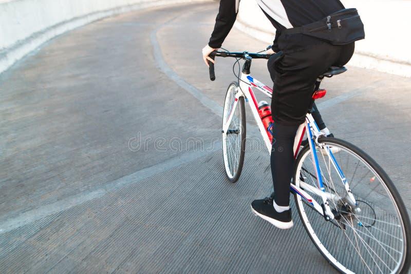 Καλλιεργημένο άτομο φωτογραφιών που οδηγά σε ένα οδικό ποδήλατο στοκ εικόνες