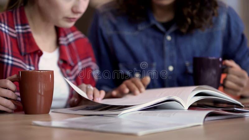 Καλύτεροι φίλοι που πίνουν το τσάι και που κοιτάζουν μέσω των εικόνων στο περιοδικό, ελεύθερος χρόνος στοκ εικόνες με δικαίωμα ελεύθερης χρήσης