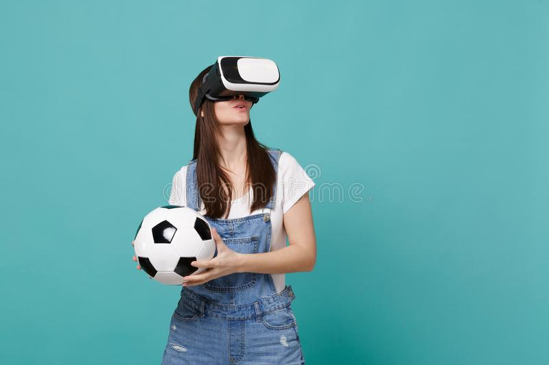 Κατάπληκτος νέος οπαδός ποδοσφαίρου γυναικών που κοιτάζει στο παιχνίδι σφαιρών ποδοσφαίρου εκμετάλλευσης κασκών που απομονώνεται  στοκ φωτογραφία με δικαίωμα ελεύθερης χρήσης