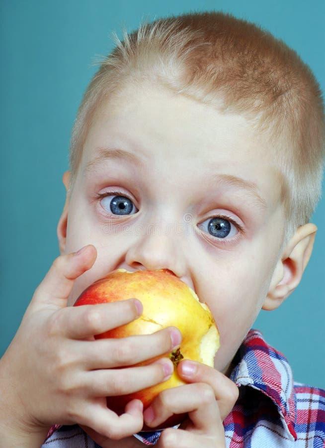 κατανάλωση παιδιών μήλων μικρό παιδί που τρώει με την όρεξη ένα μεγάλο μήλο Υγιή τρόφιμα για τα παιδιά στοκ εικόνες