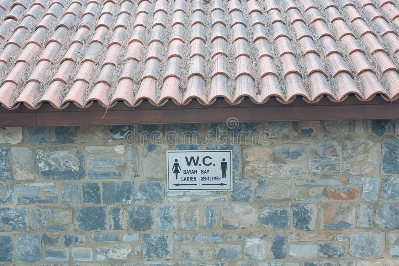 Κατευθυντικό σημάδι στην τουαλέτα στον τοίχο πετρών στοκ εικόνα