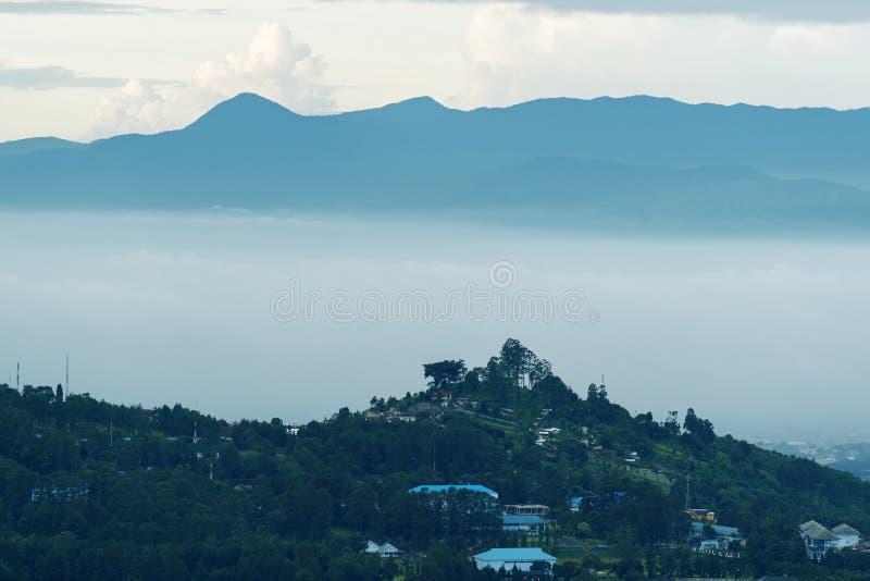 Κατοικημένα σπίτια με το misty υπόβαθρο βουνών στοκ εικόνες με δικαίωμα ελεύθερης χρήσης