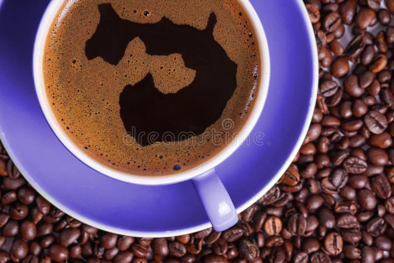 Καφές στο πορφυρό φλυτζάνι στον πίνακα που περιβάλλεται με τα φασόλια καφέ στοκ φωτογραφία με δικαίωμα ελεύθερης χρήσης